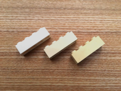 Three Lego bricks with various discolorations before cleaning